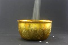 Fallender Reis in der traditionellen siamesischen goldenen Schüssel Stockbilder