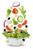 Fallender Salat in der Schüssel mit Kopfsalat, Tomaten, Zwiebel und Oliven lizenzfreies stockfoto