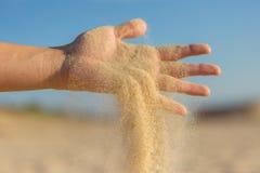Fallender Sand durch Finger Stockbild