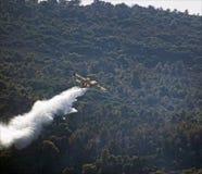 Fallendes Wasser des Feuerwehrmanplanes über einem Feuer Lizenzfreies Stockbild