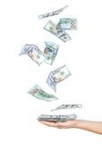 Faller dollar sedlar in i händerna Arkivbild