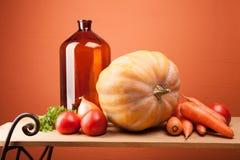 Fallernte - gelber Kürbis, Tomaten, Karotten, Zwiebeln und Kräuter auf einem hölzernen Regal Lizenzfreie Stockfotos