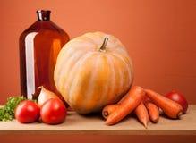 Fallernte - gelber Kürbis, Tomaten, Karotten, Zwiebeln und Kräuter auf einem hölzernen Regal Lizenzfreies Stockbild