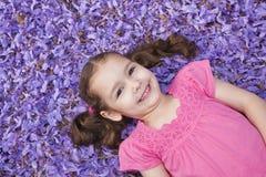 fallet liggande purpurt barn för blommaflicka arkivbild