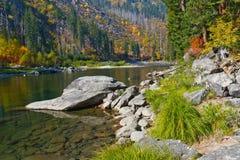 Fallfarben durch den Fluss Stockbild