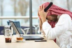 Fallimento online dell'uomo saudita arabo disperato fotografie stock