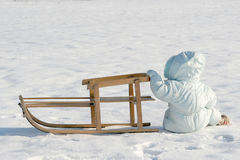 Falling. A baby sitting near the sled Royalty Free Stock Photos
