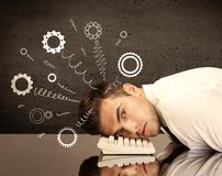 Cog wheels springing from a fed up and tired businessman`s head resting on laptop keyboard. Falling apart illustration concept with cranks, cog wheels springing royalty free stock photography