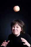 Falling of an apple. Brown-haired woman pending impact. A portrait on a black background Stock Photos