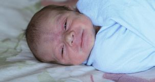 Falling asleep baby. A baby swaddled in a diaper falls asleep stock video