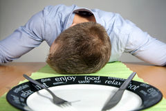 Falling asleep on a table Stock Photography