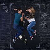 Falling asleep. Young couple falling asleep while playing a board game in a bedroom drawed with chalk on paper Stock Image