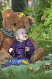 Falling autumn leaves. Happy baby girl watching falling autumn leaves stock photography