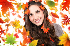 Falling autumn leaves and smiling woman stock photography