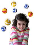 Falling Balls. Photo of colorful rubber balls falling over a pretty young girl Royalty Free Stock Photos