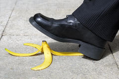 Falling on a banana skin. Businessman about to slip and fall on a banana skin royalty free stock photos