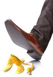 Falling on a banana skin. Businessman foot about to slip and fall on a banana skin royalty free stock photography