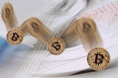 Falling bitcoin cryptocurrency exchange rate. On the blurred newspapers background stock images