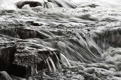 Falling blurred water. Among the stones Royalty Free Stock Image