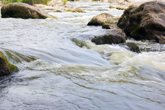 Falling blurred water among the stones Stock Image