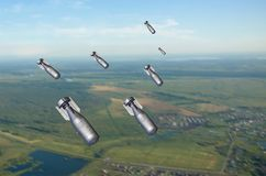 Falling bombs weapons charges dropped from a fighter combat aircraft royalty free stock images