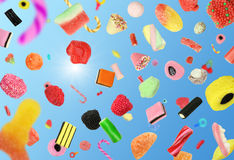 Falling Candy. Colorful candy falling in a clear blue sky royalty free stock photos
