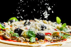 Falling cheese on a freshly prepared pizza with black olives Stock Images