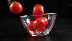 Falling cherry tomatoes in glass bowl, slow motion 250 fps stock video