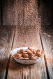Falling cocoa powder on chocolate balls Royalty Free Stock Images