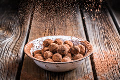 Falling cocoa powder on sweet chocolate balls Stock Images