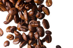 Falling coffee beans. Coffee beans fall on a white background, the grain in the background are blurred out of focus royalty free stock image
