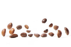 Falling coffee beans on white background Stock Photos