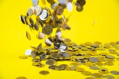 Falling coins money on yellow background, business wealth concep. T idea Stock Images