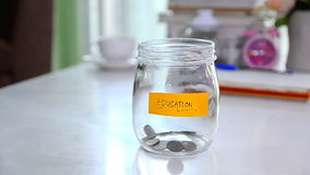 Falling of coins to glass jar concept to saving money with copyspace. HD Falling of coins to glass jar concept to saving money with copyspace stock video