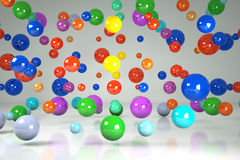 Falling colorful 3d balls. Falling colorful three-dimensional balls on a gray background Royalty Free Stock Photos
