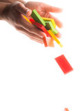 Falling colorful domino in hand Royalty Free Stock Photos