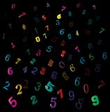 Falling colorful figures, numbers backdrop on black background.  Stock Photos