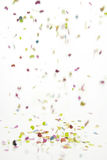 Falling confetti over white background. Photo of confetti falling down over white background with motion blur effect Royalty Free Stock Images