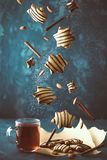 Falling cookies with hot tea. Levitation of gingerbread with chocolate sauce and cinnamon on dark background. Christmas mood Royalty Free Stock Image