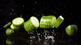 Falling cucumber cuts with water splash, slow motion. Falling cucumber cuts on black background with water splash, slow motion stock footage