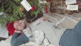 Falling dollars. A man is sleeping near a Christmas tree. Hd stock video footage