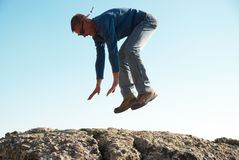 Falling down man. From the rock with blue background Stock Photos