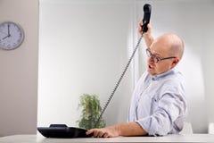 Falling down. Nerdy furious clerk smashing the phone Royalty Free Stock Photos