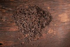 Falling dried black tea leaves isolated on wooden table. Falling dried black tea leaves isolated on wooden background royalty free stock image