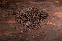 Falling dried black tea leaves isolated on wooden table. Falling dried black tea leaves isolated on wooden background stock images