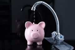 Falling Dripping Water Drop From The Faucet Inside The Piggybank. Dripping Water Droplets Are Falling In The Pink Piggybank From Kitchen Sink Faucet Stock Photography