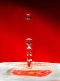 Falling drops of water over red Royalty Free Stock Images