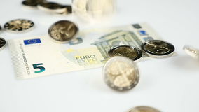 Falling Euro coins on paper currency. Falling Two Euro coins on paper currency - slow motion stock footage