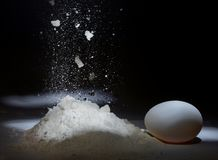 Falling flour and chicken egg on a dark background. stock photography
