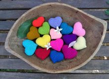 Falling flower and leaf on colourful hearts in wooden tray in the garden Stock Photos